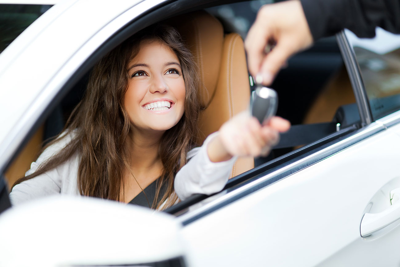 young woman getting keys to new car