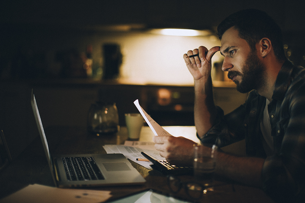 man sitting at computer reviewing finances